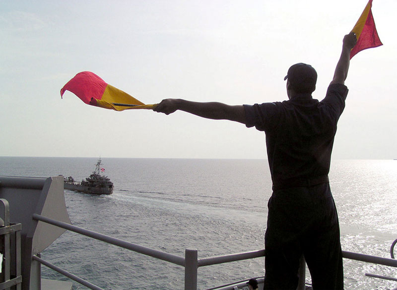 Man Waving Flags For Boat